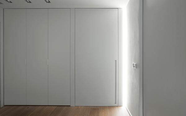 Cristina Prats Arquitectura Interiorismo Casa en Barcelona Vestíbulo luz rasante y puertas lacadas blancas
